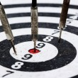 Stock Photo: Three old darts hitting target