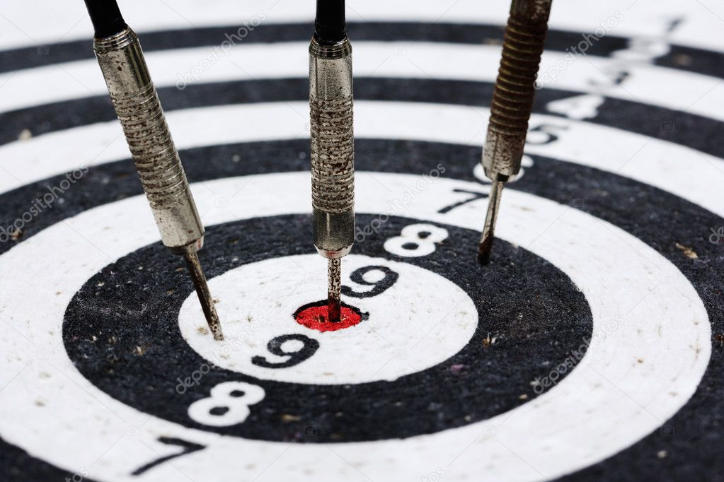 Three old rusty darts hitting the target  Stock Photo #10969924