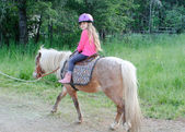Young girl riding on pony — Stock Photo