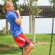 Teenage girl climbing swing chain — Stock fotografie