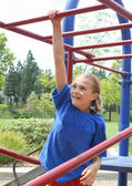Apprehensive preteen female on bars — ストック写真