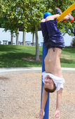 Boy hanging upside down in park — Stock Photo