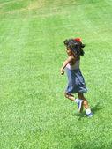 Happy hispanic girl running in park — Stock Photo