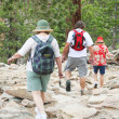 Three boulder jumping baby boomer hikers — Stock Photo