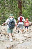 Three boulder jumping baby boomer hikers — Stock Photo