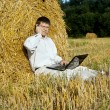Businessman with laptop near the haystacks — Stock Photo