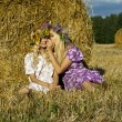 Girl sitting near a haystack in the field — Stock Photo