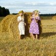 Two girls in a field near haystacks — Stock Photo