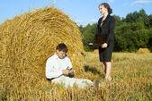 Boss and secretary in the nature near the haystacks — Stock Photo