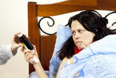 Girl lies in bed sick with common cold thermometer — Stock Photo