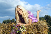Girl lying on a haystack — Stock Photo