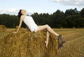 Girl on a haystack — Stock Photo