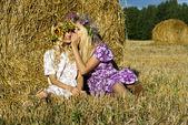 Happy girl sitting near the haystacks — Stock Photo