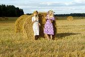 Dos chicas en un campo cerca de pajares — Foto de Stock