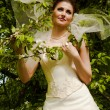 Beautiful bride with green foliage — Stock Photo