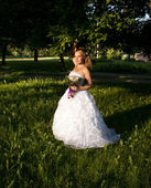 Beautiful girl in a wedding dress with bouquet — Stock Photo