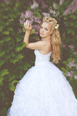Beautiful girl in a wedding dress with lilac — Stock Photo