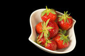 Fresh strawberries in white bowl on a black background. — Stock Photo