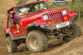 Red off-road car in difficult terrain — 图库照片