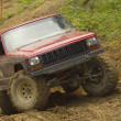 Red off-road car in terrain. — Stock Photo