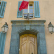 The entrance door to the building with a French flag. - Stock Photo