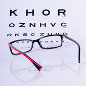 Reading eyeglasses and eye chart — Stock Photo