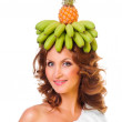 Royalty-Free Stock Photo: Pretty girl with bananas and pineapple over head