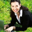 Happy business woman working with notebook laying on grass — Stock Photo