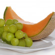 Cantaloupe and green grapes on white plate — Stock Photo