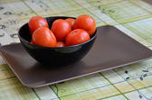 Black bowl full of tomatoes — Stock Photo