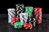 Stack of casino gambling chips on keyboard — Stock Photo