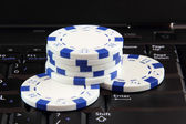 Stack of white casino gambling chips on keyboard — Stock Photo