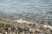 Wet pebbles at sea shore — Foto Stock