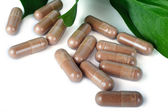 A lot of brown capsules on white background — Stock Photo