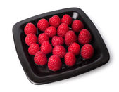 Raspberries on a black plate isolated on white background — Stock Photo