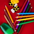 Colored pencils, erasers, sharpeners isolated on red background — Stock Photo #11614713