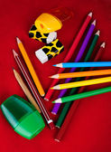 Colored pencils, erasers, sharpeners isolated on red background — Stock Photo