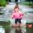 Girl jumps into a puddle — Stock fotografie
