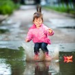 Stock Photo: Girl jumps into puddle