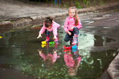 Girls playing in puddle — Stock Photo