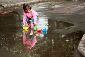 Girl playing in puddle — Stock Photo