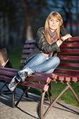 Menina em um parque da cidade em um banco — Foto Stock