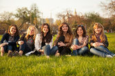 Happy smiling group sitting on the grass — Stock Photo