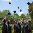 Graduates throwing  into the sky academic caps — Stock Photo