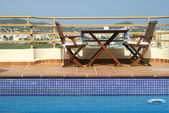 Table and Chairs by Swimming Pool in Roof Garden in Mediterranean City — Stock Photo