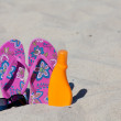 A pair pink colored Flip-Flops in the sand with a black sunglasses and sun milk — Stock Photo