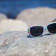 Sunglasses with colorful floral eyeglass frame lies on rock on coast — Stock Photo #11038784
