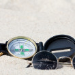 A compass and sunglasses lying on the hot desert sand — Stok fotoğraf
