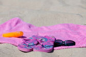 With flip-flops, beach towel, sun cream and sunglasses on the beach — Stock Photo