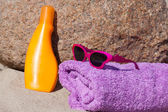 Bath towel, sunscreen and sunglasses are on a rock on the beach — 图库照片